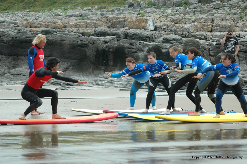A group of girls enjoying a surfing lesson in Bridgend